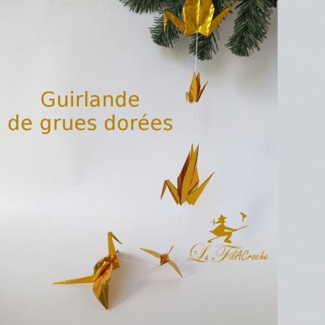 Guirlande de grues dorées en origami.