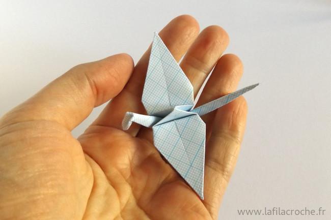 Grue origami en papier millimetré dans une main