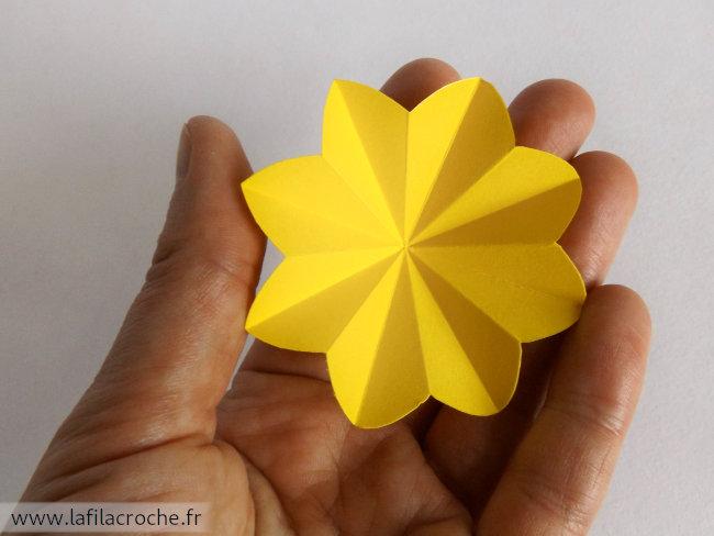 Fleur origami dans la main pour montrer la taille